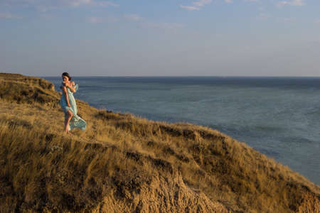 A pretty girl in a long blue dress walking on a high cliff by the sea or ocean on sunny windy summer day. Young beautiful woman with short hair watching sunset on the shores of the calm sea.