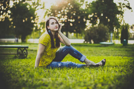 Young beautiful woman in yellow blouse and blue jeans sitting in a park on the grass holding head on hand and smiles in the warm summer evening. Photo of a girl with back sunlight on the nature.