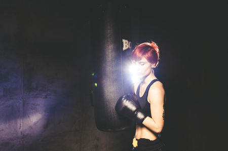 woman handle success: young woman boxer standing near punching bag