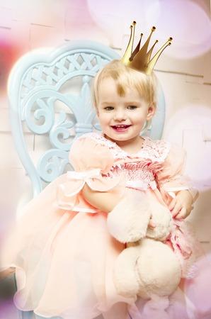 Beautiful happy little princess posing in studio