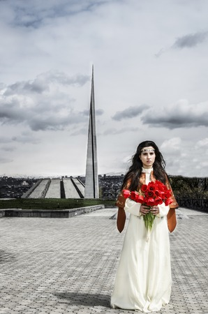 Girl with red beautiful tulips standing in Tsitsernakaberd near Armenian genocide memorial and looking forward.