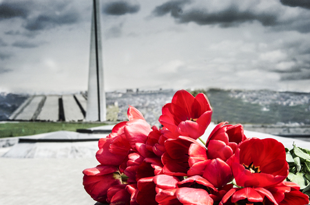 Red tulips in Tsitsernakaberd with Armenian genocide memorial on background.