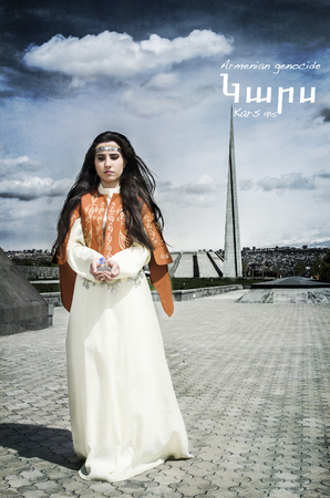 Girl in national dress standing in Tsitsernakaberd near Armenian genocide memorial with land in hands from past Armenian lands.
