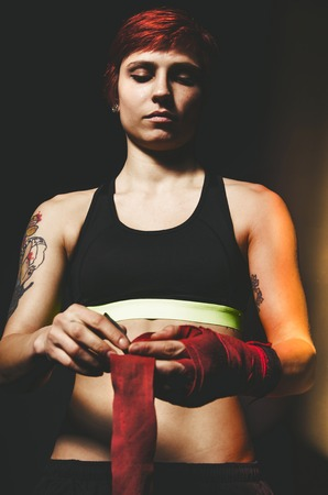 woman handle success: young tattooed woman boxer with hands wraps close up portrait Stock Photo