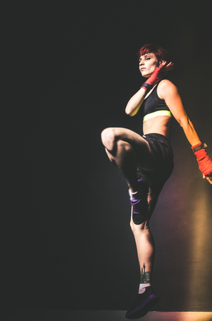 punched out: young tattooed woman boxer jumping close up portrait
