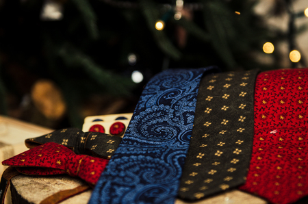 Set of beautiful men accessories of bow tie, neck tie, cufflinks, mans scarf with present box on christmas tree background