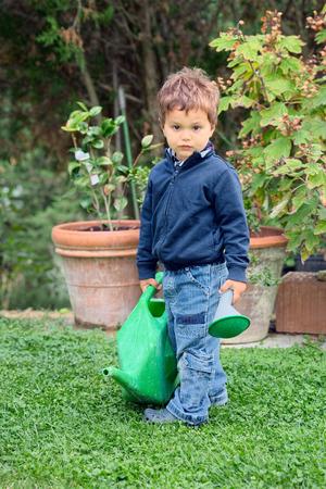 bambino: Bambino con annaffiatoio verde smontato si appresta ad innaffiare piante
