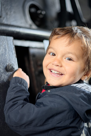 curiously: Child plays curiously observing the inside of the boiler of old steam locomotive