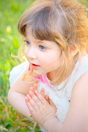 girl squatting: Little blonde girl in white dress, squatting on a lawn busy praying hands folded Stock Photo