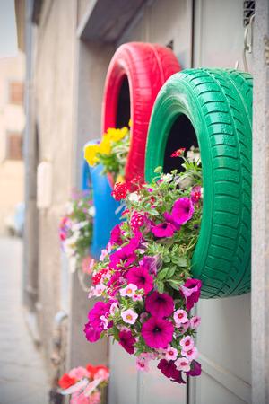 reciclar: M�todo ingenioso, original y ecol�gico de reciclaje de neum�ticos de coche como plantadores (detalle del rojo y verde) Foto de archivo