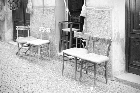 marked down: Chairs marked with the name of the customer left the entrance to the bar overlooking the street Stock Photo