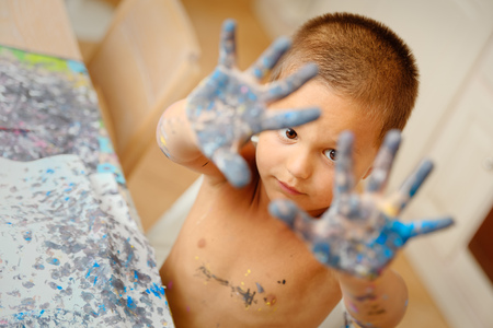 smeared hand: Child shows his hands dirty color while drawing lessons at school Stock Photo