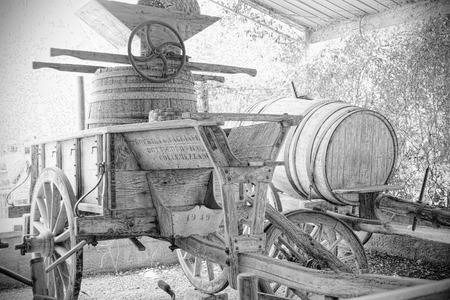 winepress: Ancient winepress for harvest mounted on a barrel ready for transport by cart, in a farm shed BW Stock Photo