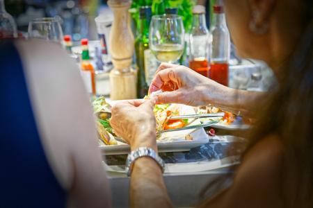 restaurateur: Girl slips with his hands a crustacean of his shrimp dish