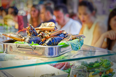 restaurateur: Tray on top of lobsters, the blurry background hungry people waiting