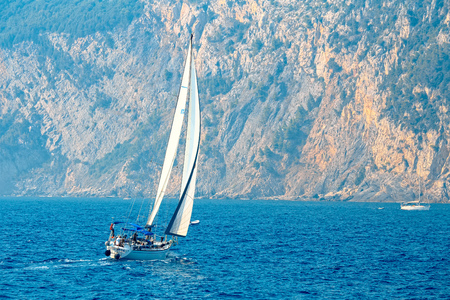 inshore: Sailboat navigates in the inshore waters of the nature park of the 5 Terre, Liguria, Italy Stock Photo