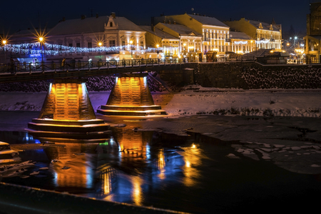 The European night city in the winter - in the foreground the river and the pedestrian bridge. In the river beautifully reflected night color lights
