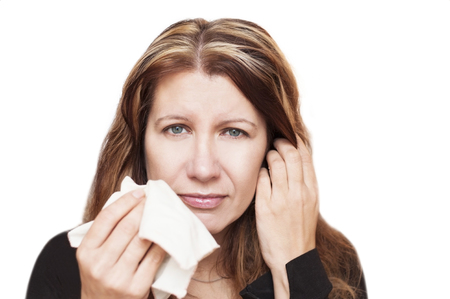 Affected by cold woman wipes his nose with handkerchief on white background. The woman has a sad and unhealthy appearance. Isolated