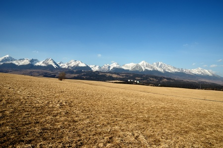 High Tatras, Slovakia plowed field in the foreground and blue sky