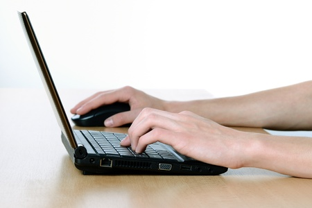hands and netbook on the office desk, isolated background