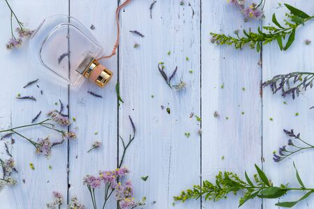 Perfume bottle surrounded by fresh flowers on wooden background Banque d'images