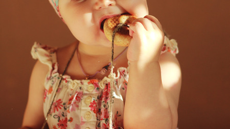 Cute unrecognizable baby girl eating yummy donut Stock Photo