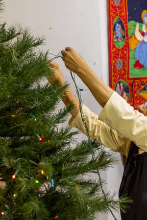 Older woman putting lights and spheres on the Christmas tree