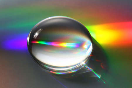 prism: A giant water droplet reflects and refracts incident light forming beautfiul rainbow reflections. Shallow D.O.F with focus located near the bottom edge of the bubble.