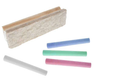 Several chalk sticks next to a board eraser. Isolated on White. White space at the right. Focus at the front.
