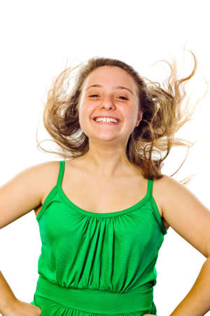 Girl with a big smile on her face and her hair blowing. White background.