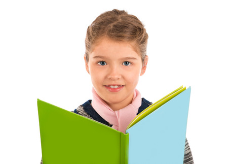 A cute little girl holding a big storybook looking at the camera and smiling  Isolated on white