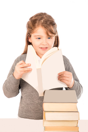 A small girl with a gray school uniform reading a book  Pile of books in a table in front of her  Isolated on white