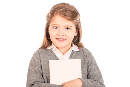 A small girl wearing a gray school uniform hugging a blanked out book looking at the camera  Isolated on white  Stock Photo