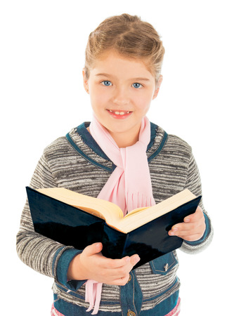A little girl standing and holding a big book  Smiling and looking at the camera  Isolated on white background