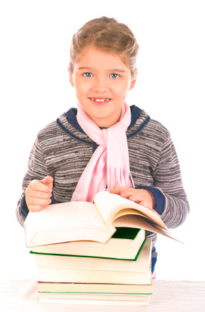 Little girl looking at the camera smiling with an open book on top of a pile of closed books on a table  Isolated on white
