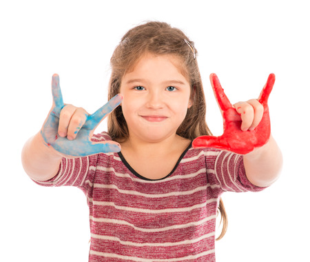 Cute little girl playing with red and blue paint showing her fingers.