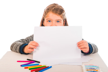 A little girl showing a piece of paper. Colored crayons and paint on the table.