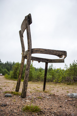 Abandoned chair in the forest against the blue sky
