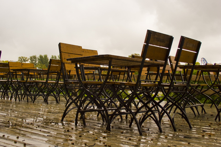 Empty brown tables and chairs in a cafe on the terrace in the rain