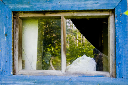 broken window of a house in blue frame