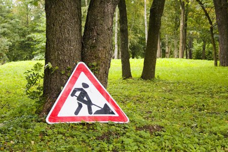 tree removal service: Road repair sign in the forest on the ground in summer Stock Photo