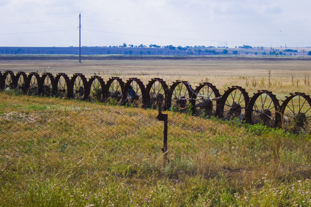 Fence and fence of old wheels on the field Stock Photo