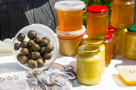 Honey in jars and propolis balls on the counter