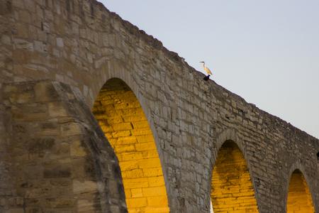 aqueduto longo com arcos ao pôr do sol em Larnaca, Chipre com pássaros no topo