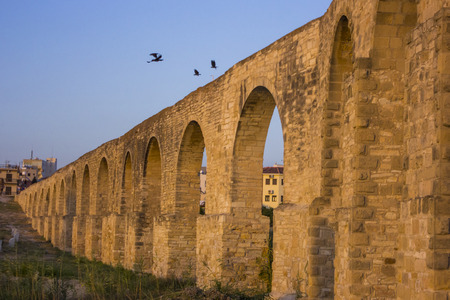 long aqueduct with arches at sunset in Larnaca, Cyprus with birds on top Stock Photo