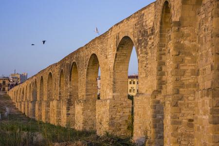 largo acueducto con arcos al atardecer en Larnaca, Chipre con aves en la parte superior