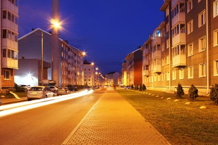 Empty street of town lit by street lights at night.