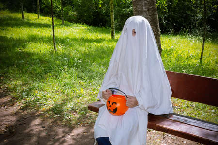Child in halloween white ghost costume with a basket of pumpkin sitting on park bench