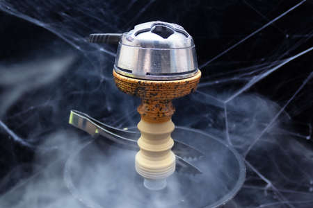 Bowl of hookah with kaloud lotus, saucer and tongs, smoke around, black background with spider web.