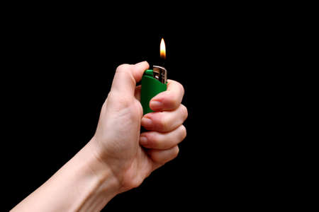 Human hand holding green lighter with burning flame on black backdrop. Little fire. Isolated on a black background.